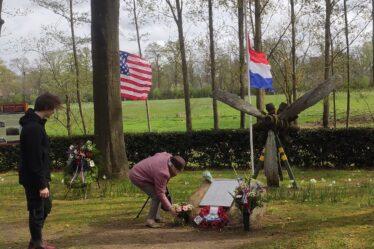 Een oude dame bukt om bloemen te leggen bij een steen met een plakette van slachtoffers in de Tweede Wereldoorlog in Herkenbosch. Een jongeman van een jaar of 18 kijkt toe.Op de achtergrond bomen, een grasveld en de wapperende vlaggen van Nederland, Engeland en de Verenigde Staten.
